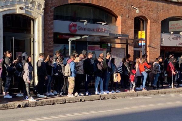 La file d'attente sur le trottoir devant l'arrêt de bus François Verdier.