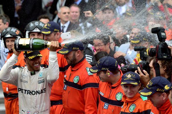 Le pilote anglais Lewis Hamilton de l'équipe Mercedes AMG Petronas verse du champagne pour célébrer sa victoire au Grand prix de Monaco en mai 2016.