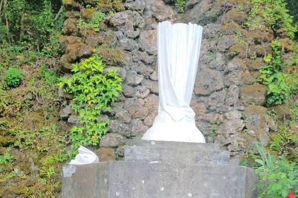 A gauche de la statue, la tête gisante après l'acte de vandalisme qui a décapité l'oeuvre au pont d'Hérault de Sumène.