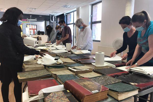 Les équipes de la médiathèque de Beauvais tentent de sauver les livres des fonds patrimoniaux en intercalant des feuilles absorbantes entre les pages.
