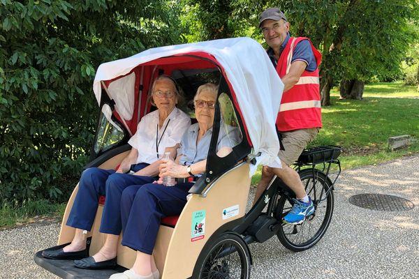 """Jacqueline, 90 ans, et Henriette, 93 ans, partagent une balade dans le parc du Bourran avec George, bénévole de """"À vélo sans âge""""."""