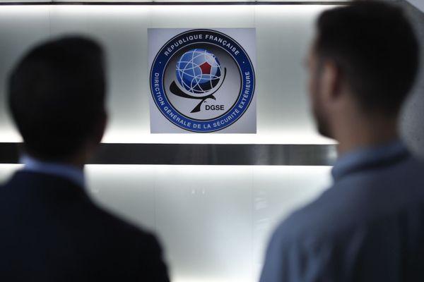Deux hommes devant le logo de la DGSE - Photo d'illustration