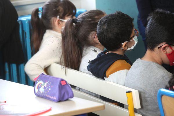 Des écoliers d'une classe de cp qui portent le masque dans une école élémentaire alsacienne