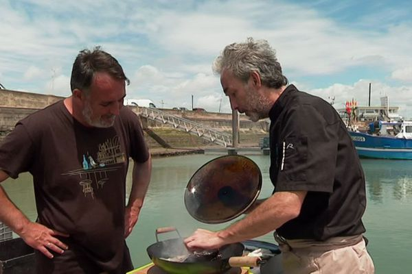 Yann Salaün avec le cuisinier Fabrice Gass en pleine préparation de maigre fumé sur le port de Royan.