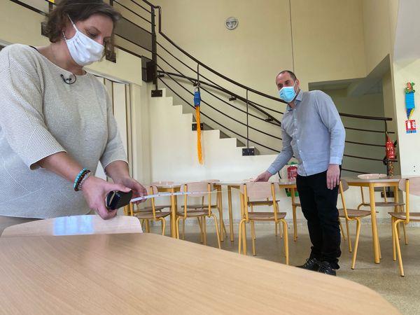Agnès Bibi Albarede, directrice de l'école des Clauzades à Lavaur (Tarn), actuellement fermée pour cause de covid, mesure la distance entre les tables avec l'aide du directeur de la cuisine centrale.