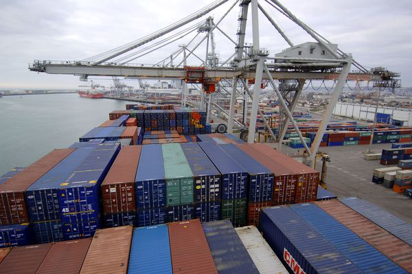 """Symbole de cette mondialisation, les porte-conteneurs qui traversent la planète. Ici cargaison du navire  Otello, le plus grand navire français de cette catégorie avec une longueur de 334 mètres et une capacité de 8.500 """"boîtes"""", le 23 décembre 2005 au Havre."""