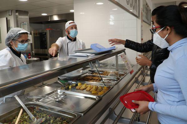 Des étudiants retirent des plats chauds à emporter dans un Resto U