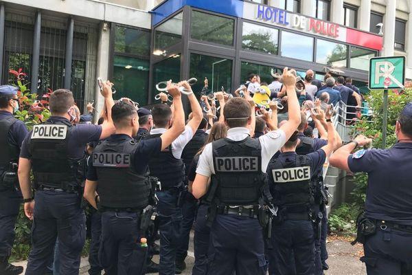 Les policiers de Grenoble, brandissant leurs paires de menottes, lors de leur courte manifestation ce jeudi 11 juin devant le commissariat central.