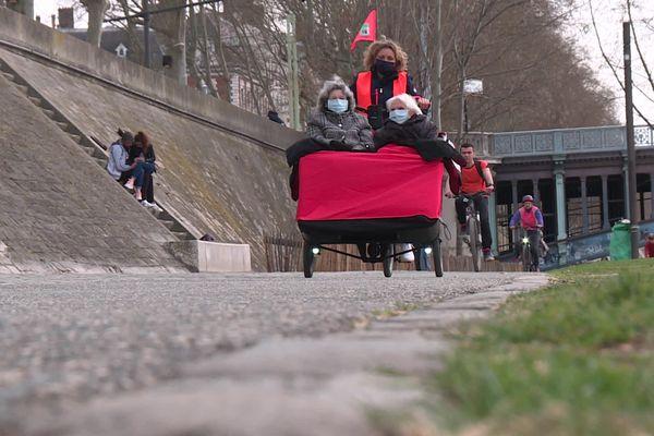 Les bénévoles de l'association A vélo sans âge promènent des personnes âgées dans la ville à triporteur.