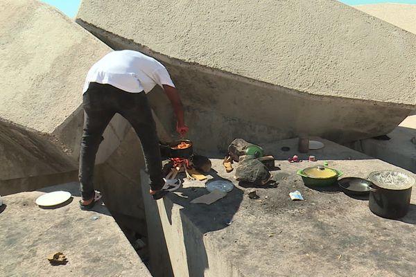 Osas Oio prépare son repas sur la digue du port