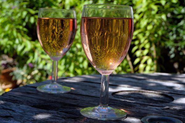 Deux verres de vin rosé sur une table, à l'ombre (Image d'illustration).