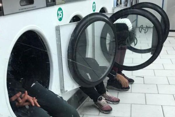 De jeunes hommes assis dans les machines d'une laverie du quartier de la Goutte-d'Or, dans le 18e arrondissement de Paris, le 20 décembre 2017.