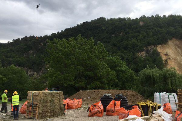 L'hélicoptère, dans le ciel, emporte vivres et matériel pour aider les villageois.