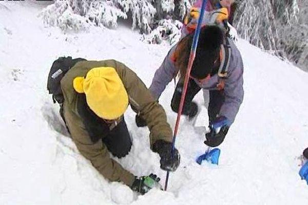 Ce stagiaire a dans les mains un petit boîtier appelé DVA (détecteur de victimes d'avalanches)