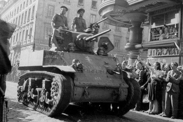 Le 3 septembre 1944, des résistants français défilent rue de la République dans un blindé, pris aux Allemands, sur lequel a été peinte en hâte une croix de Lorraine