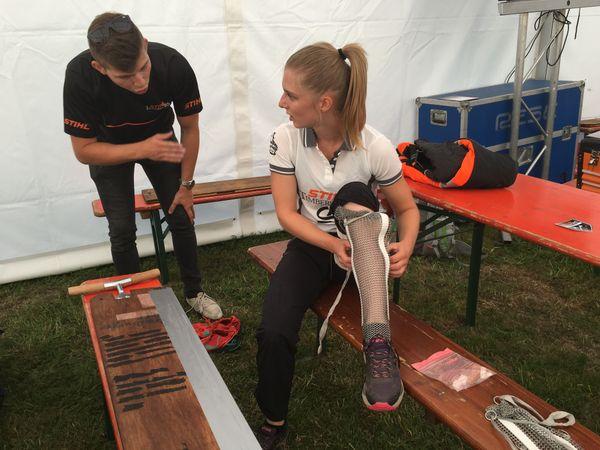 Aude Seel, 22 ans, protège ses jambes et ses pieds avec de la cotte de maille avant la compétition de bûcheronnage