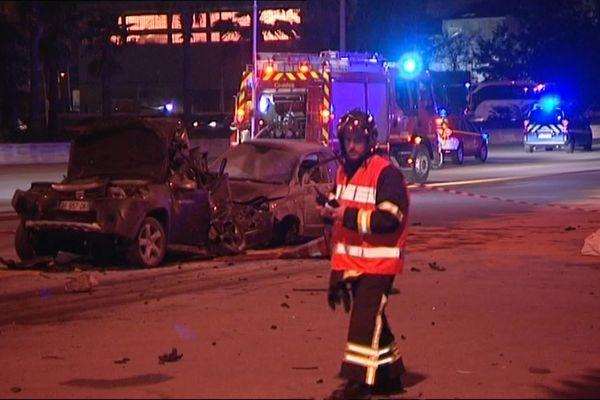 Un pompier devant des carcasses de véhicules au péage de Saint-Isidore.