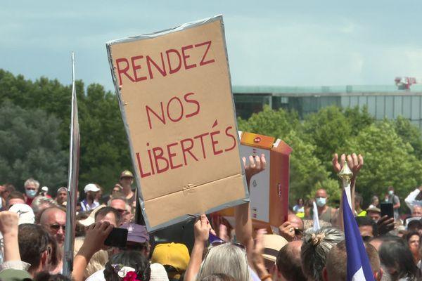 """À Bordeaux, un manifestant brandit un panneau sur lequel on peut lire """"rendez nos libertés""""."""