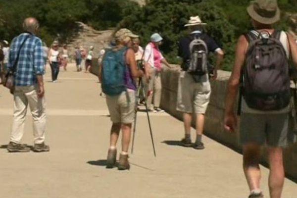 chaussures de marche, sacs à dos et chapeau pour ces randonneurs du Pont du Gard