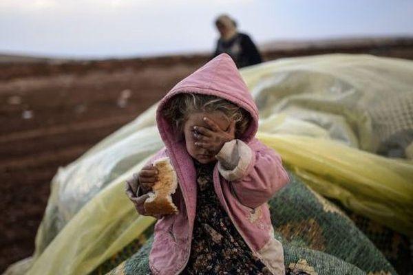 Près de Suruc, ville du sud¬est, province de Sanliurfa, Turquie, 2 octobre 2014. Une femme kurde et sa fille attendent après leur passage de Syrie en Turquie, sous les tirs de mortier venant des deux côtés.