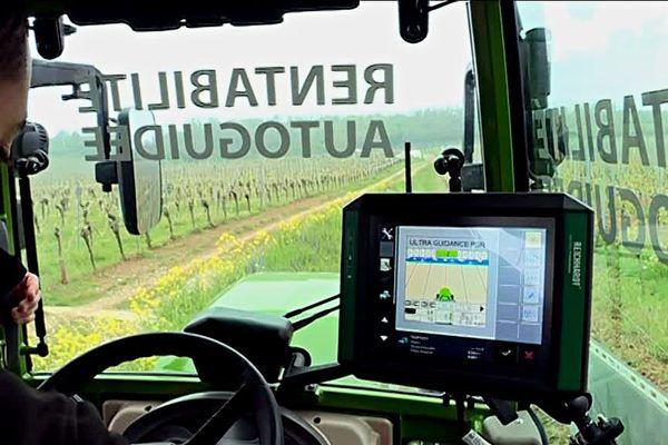 Dans sa cabine de tracteur autoguidé, l'opérateur, via une console numérique, se libère de la tâche de la trajectoire dans les rangs de vigne.