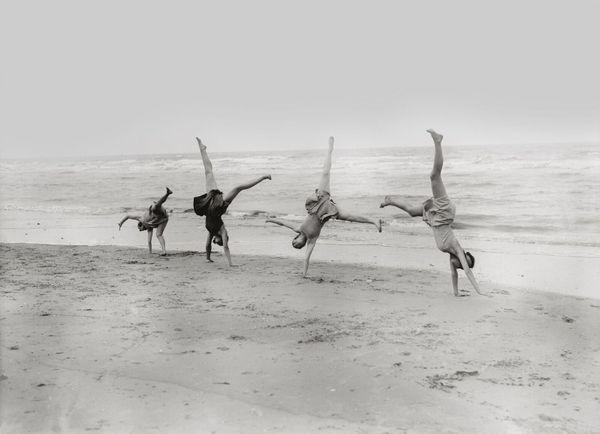 SAINT-IDESBALD, BELGIQUE, 1929. Quatre danseurs appartenant au Margaret Morris Movement s'entraînent à faire la roue sur le rivage. Influencée par le travail d'Isadora Duncan, Margaret Morris avait fondé sa propre écolede danse à Londres et traversait régulièrement la Manche pour faire découvrir les plages belges à ses élèves.