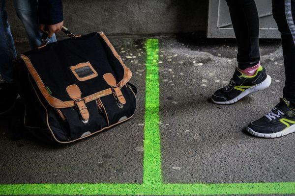 Deux élèves séparés par une ligne marquant la distanciation sociale. Photo d'illustration.