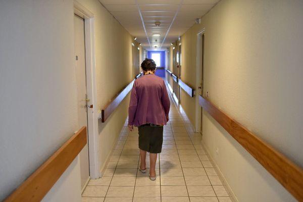 Illustration. Dans une maison de retraite, une résidente marche seule dans un couloir.