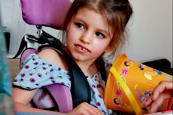 Lexane, 7 ans, ne peut pas se tenir assise ou debout toute seule. Elle a besoin en permanence d'équipements adaptés.