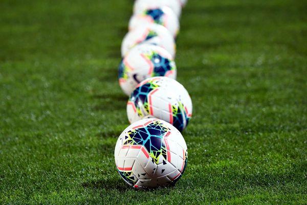 Des ballons alignés sur un gazon - Photo d'illustration