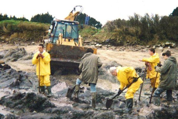 Des bénévoles ramassent à mains nues les galettes de mazout au large des côtes bretonnes.