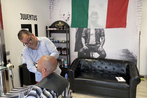 """Dans son salon de la banlieue grenobloise, Salvatore en oublierait presque d'arrêter sa tondeuse quand il parle de la """"partita"""" de ce soir. Heureusement, ce client là est seulement venu se faire tailler la barbe."""