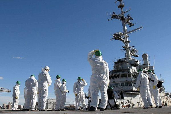 Un groupe de journalistes, réunis le 19 novembre 2004 dans le port militaire de Toulon, avant d'assister aux premiers travaux de désamiantage de l'ancien porte-avions