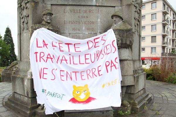 Banderole du 1er mai accrochée sur le monument aux morts de la place Carnot de Rouen