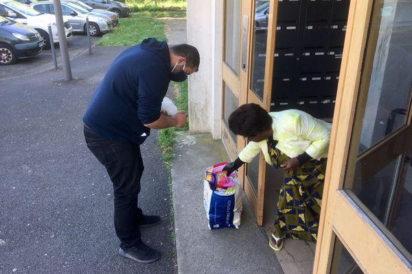 Cette habitante du quartier des Trois Cités à Poitiers récupère un sac de courses préparé par Youssef Maiza, qui a lancé le réseau solidaire Entraides Citoyennes 86.