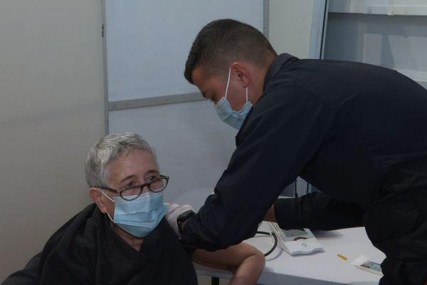 Un pompier de Paris délivre une dose de vaccin à une patiente ce samedi à Saint-Denis.