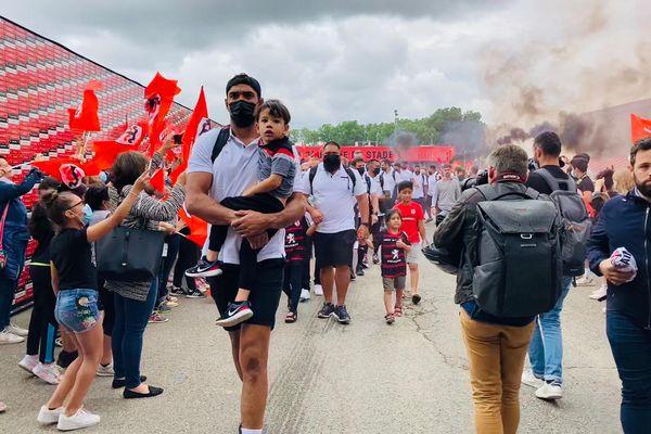 Toulouse - Drapeaux rouges et noirs et fumigènes : les supporters encouragent les joueurs du Stade Toulousain à leur départ pour la finale du Top 14 au Stade de France. 23 juin 2021.