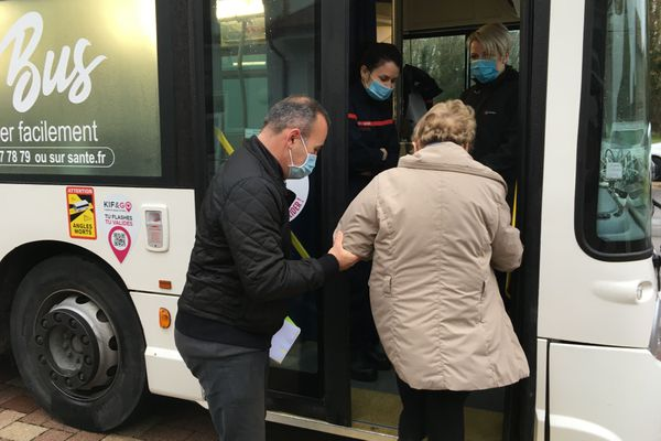 L'adjoint au maire, l'infirmière, et la conductrice font grimper Josiane dans le bus.