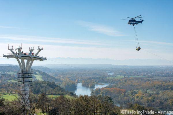 Un hélicoptère a permis de hisser certains rouleaux de câbles pour les amener jusqu'au sommet d'un pylône.