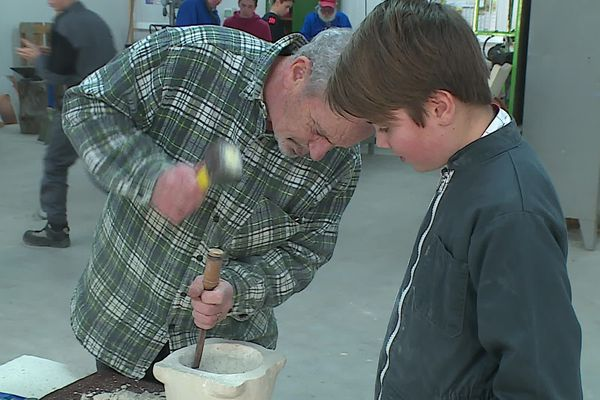 Un des artisans bénévoles de l'association, tailleur de pierre de métier, fait découvrir les gestes précis de son métier.