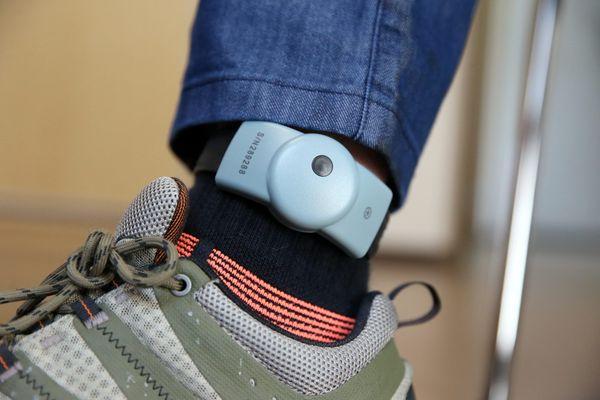 Un bracelet de surveillance électronique ou anti-rapprochement fixé à la cheville d'un homme. Dispositif de surveillance électronique qui permet de géolocaliser une victime et un auteur de violence conjugale.