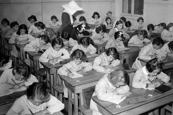 Photo datée du 28 septembre 1957, en France, d'une classe primaire de petites filles faisant une dictée.