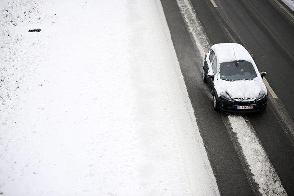 Une voiture enneigée s'arrête sur le bord de l'autoroute - Photo d'illustration