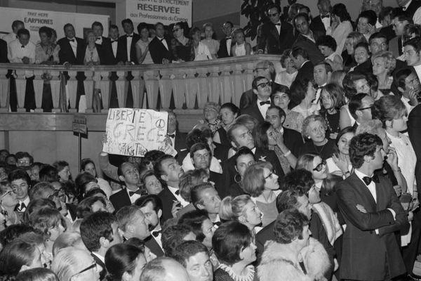"""Des manifestants brandissant des pancartes demandant la """"libération de la Grèce de l'emprise des colonels"""", pénètrent le 22 mai 1968 dans le Palais des Festivals à Cannes, lors de la projection du film """"Z"""" de Costa Gravas."""