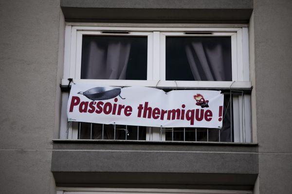 """Une banderole """"passoire thermique !"""" accrochée au balcon d'un HLM."""