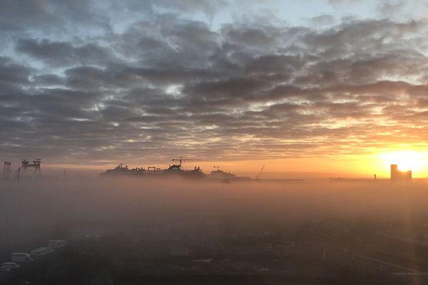 Le soleil se lève sur le port de Saint-Nazaire, encore emmitouflé dans une écharpe de brume.