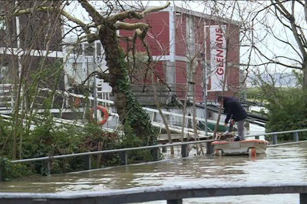 La Seine a beau monter, les employés de l'école de voile Les Glénans continuent à travailler sur leur péniche.