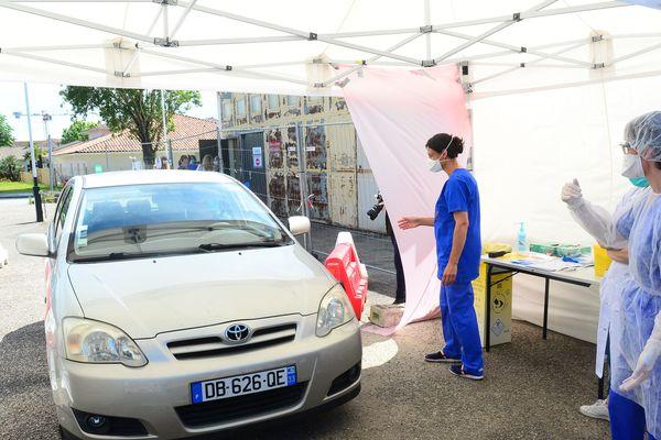 """Un automobiliste s'avance dans un """"drive"""" de dépistage du Covid-19 à Bordeaux."""