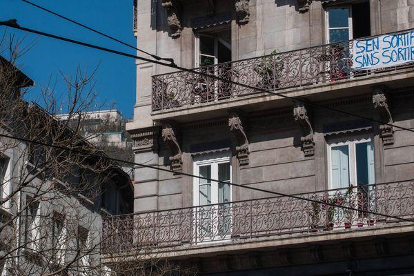 """Sur un balcon de la place Sainte-Claire, une banderole """"S'en sortir sans sortir"""" a été affichée."""