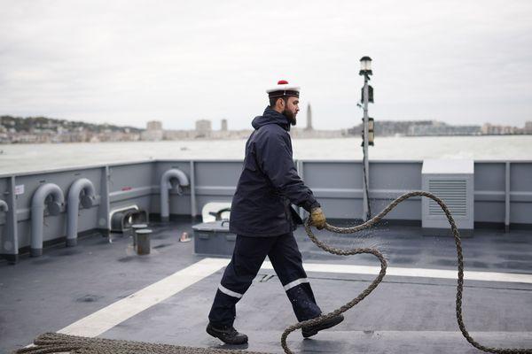 Après avoir quitté le port du Havre, un marin enroule minutieusement l'amarre sur le pont du PSP le Flamant.